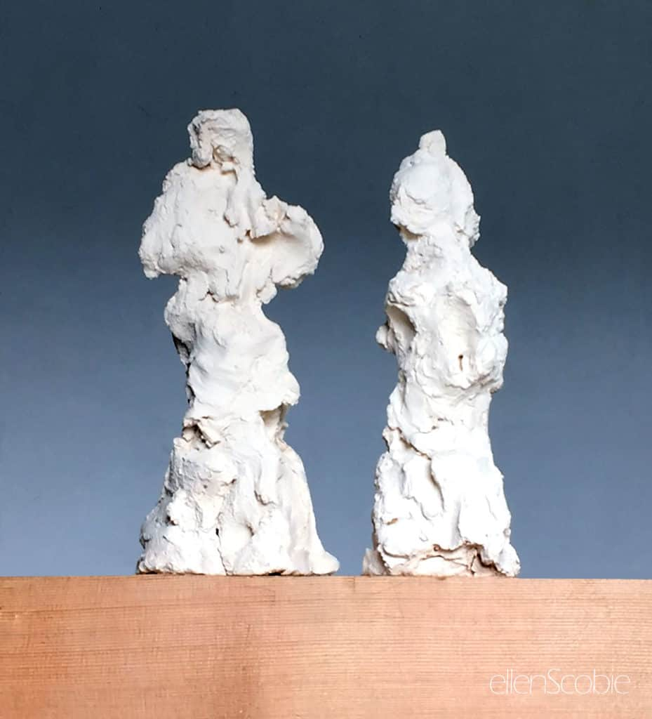 two terracotta figures on wood base