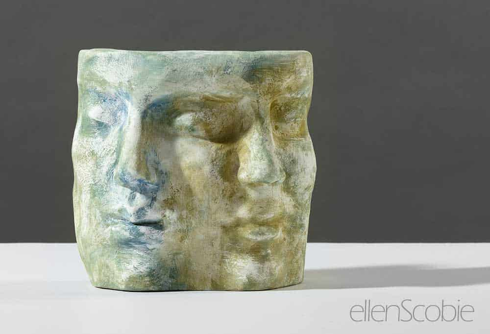 terracotta sculpture with blue and green cold finish of two faces